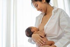 Madre asiatica con sorridere per dare allattar al senoe neonato con la camicia bianca e seduta sul fondo bianco del letto delle f fotografia stock