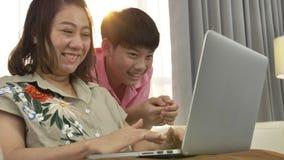 Madre asiatica e figlio che guardano sul computer portatile con il fronte di sorriso video d archivio