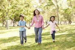 Madre asiática y niños que corren de común acuerdo en parque Imagenes de archivo