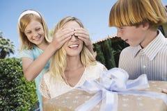 Madre asombrosamente de los niños con un regalo Imagen de archivo