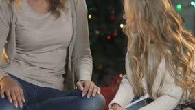 Madre atractiva que ayuda a poca hija a escribir la letra a Santa Claus, niñez almacen de metraje de vídeo