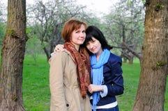 Madre atractiva y su hija en jardín Fotos de archivo