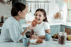 Madre attenta che alimenta un bambino con un croissant immagine stock