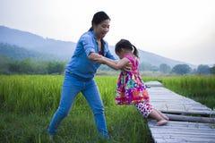 Madre ayudar a su ni?o a cruzar la corriente, hija de elevaci?n de la madre en campo del arroz foto de archivo