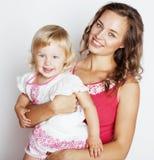 Madre bastante elegante con la pequeña hija linda que abraza, familia sonriente feliz, concepto de los jóvenes de la gente de la  Foto de archivo libre de regalías