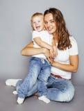 Madre bastante elegante con la pequeña hija rubia linda que abraza, familia sonriente feliz, concepto de los jóvenes de la gente  Fotografía de archivo