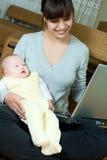 Madre, bebé y computadora portátil Imagenes de archivo