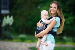 Madre bonita con el bebé en honda que camina en parque verde imagen de archivo libre de regalías