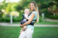 Madre bonita con el bebé en honda que camina en parque verde fotos de archivo libres de regalías