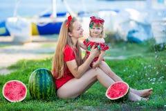 Madre bonita joven que juega con su pequeña hija linda en la playa Mamá de amor que se divierte con su niño en la orilla de mar c fotografía de archivo libre de regalías