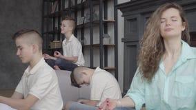 Madre bonita joven que se sienta en la sala de estar con sus tres hijos adolescentes que meditan junto Mujer y sus niños junto almacen de video