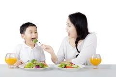 Madre bonita que alimenta a su hijo en estudio Fotografía de archivo