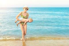 Madre calva hermosa joven que lleva a cabo el agua azul clara caucásica linda del niño pequeño en la playa tropical con lluvia ca foto de archivo