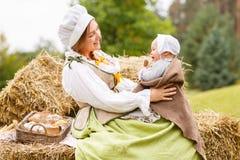 Madre campesina con el pequeño bebé en el verano que juega en pajar en el campo fotografía de archivo libre de regalías