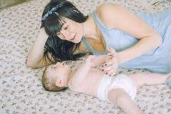 Madre cariñosa con su pequeño bebé en la cama Fotos de archivo