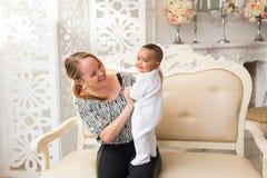 Madre cariñosa que celebra al bebé de la raza mixta en casa foto de archivo libre de regalías