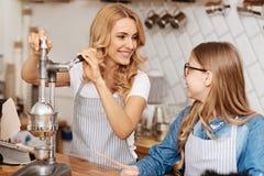 Madre cariñosa que explica a su hija cómo utilizar un dispositivo de café-fabricación Imagen de archivo