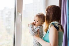Madre cariñosa que juega con su hijo del bebé cerca de una ventana Imagenes de archivo