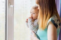 Madre cariñosa que juega con su hijo del bebé cerca de una ventana Fotos de archivo libres de regalías