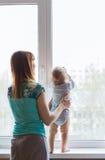 Madre cariñosa que juega con su hijo del bebé cerca de una ventana Fotos de archivo