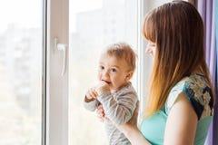 Madre cariñosa que juega con su hijo del bebé cerca de una ventana Foto de archivo libre de regalías