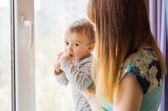 Madre cariñosa que juega con su hijo del bebé cerca de una ventana Foto de archivo