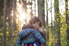 Madre cariñosa que lleva a su niño joven Fotos de archivo