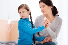 Madre cariñosa que persuade a su niño de tomar los descensos nasales imagenes de archivo