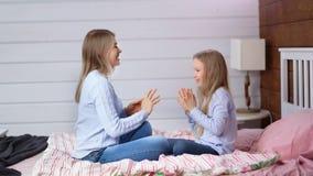 Madre casuale della foto a figura intera e daugher sveglio del bambino che godono imbrogliando le mani d'applauso che si siedono  video d archivio
