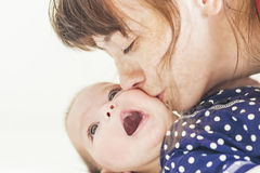 Madre caucásica feliz que besa a su pequeño niño recién nacido Imágenes de archivo libres de regalías