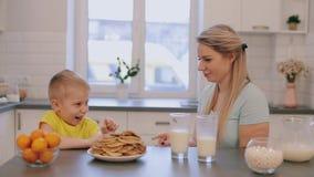 Madre caucásica hermosa feliz que se divierte con su hijo en la cocina blanca y que lo da alto-cinco almacen de video