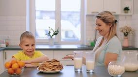 Madre caucásica hermosa feliz que se divierte con su hijo en la cocina blanca y que lo da alto-cinco almacen de metraje de vídeo