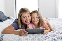 Madre caucásica rubia joven que miente en cama con su dulce joven 7 años de la hija que usa Internet en el cojín digital de la ta imagenes de archivo