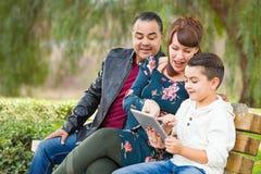 Madre caucásica y padre hispánico Using Computer Tablet con aire libre del hijo de la raza mixta fotos de archivo libres de regalías