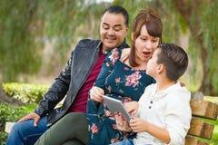 Madre caucasica e padre ispano Using Computer Tablet con l'aria aperta del figlio della corsa mista fotografie stock