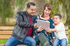 Madre caucasica emozionante e padre ispano Using Computer Tablet con l'aria aperta del figlio della corsa mista fotografia stock libera da diritti
