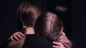 Madre che abbraccia bambina spaventata nella stanza scura, vittime della mafia, rapimento stock footage