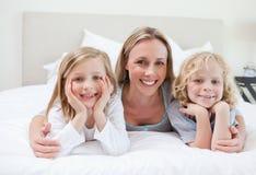 Madre che abbraccia i suoi bambini Fotografia Stock