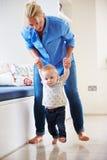 Madre che aiuta giovane figlio come impara camminare Fotografie Stock Libere da Diritti