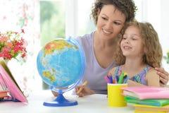 Madre che aiuta la sua figlia con lavoro Fotografia Stock