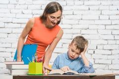 Madre che aiuta suo figlio a fare il compito della scuola Immagine Stock