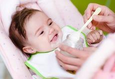 Madre che alimenta figlia neonata con il biberon Fotografie Stock