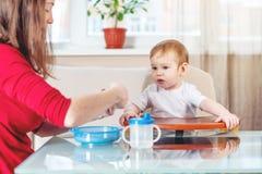 Madre che alimenta il bambino che dà la sua mano con un cucchiaio di porridge nella cucina Emozioni di un bambino mentre mangiand fotografie stock