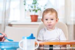 Madre che alimenta il bambino che dà la sua mano con un cucchiaio di porridge nella cucina Emozioni di un bambino mentre mangiand fotografia stock libera da diritti