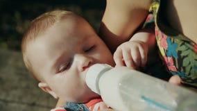 Madre che alimenta il suo bambino in natura all'aperto video d archivio