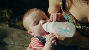 Madre che alimenta il suo bambino in natura all'aperto archivi video