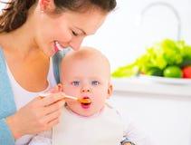 Madre che alimenta la sua neonata con un cucchiaio immagini stock