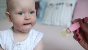Madre che alimenta la sua neonata con un cucchiaio Generi dare l'alimento al suo bambino adorabile a casa stock footage