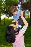 Madre che alza il suo bambino in foresta Fotografie Stock Libere da Diritti