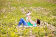 Madre che alza la sua piccola figlia in su Immagini Stock